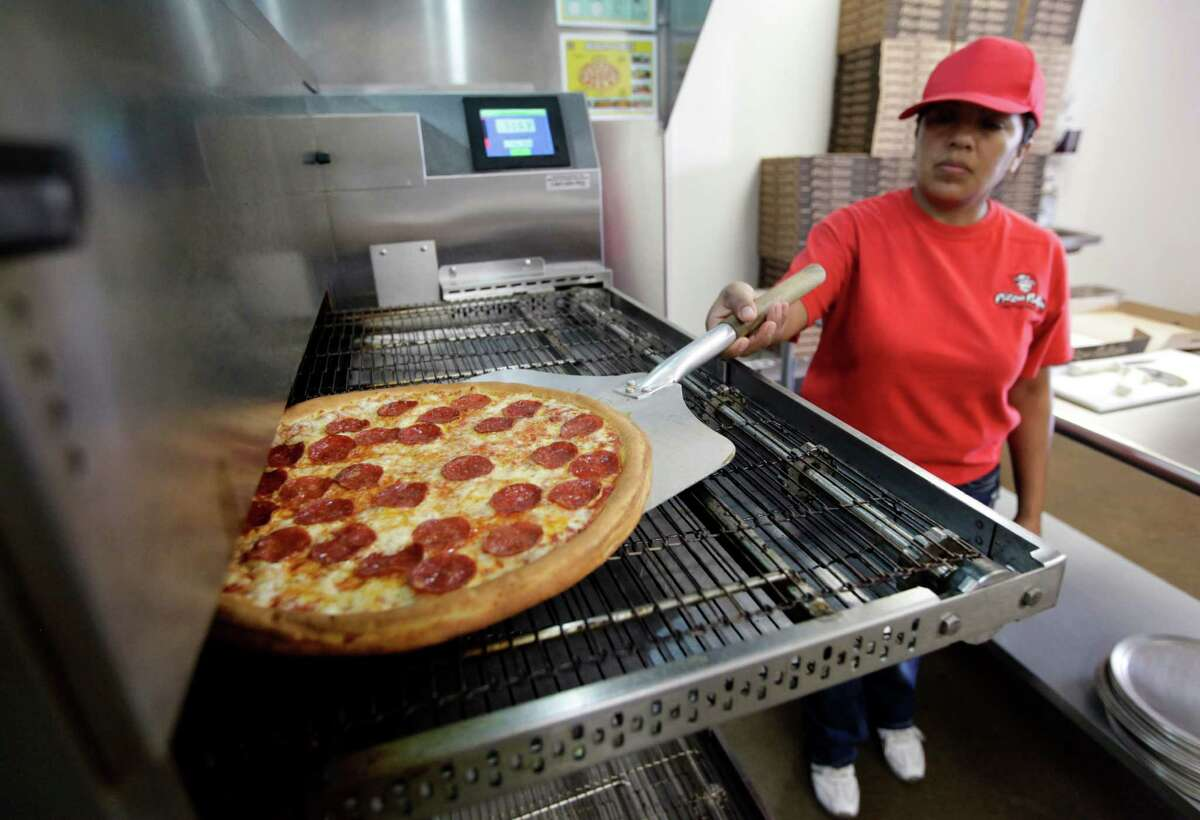 Employee Rosy Tirado pulls a pepperoni pizza from an oven at a Pizza Patron Dallas, Texas, Thursday, May 24, 2012. The fast food restaurant has drawn the attention of the Texas community for its advertising campaigns aimed at first-generation Mexican immigrants and Mexican-Americans. Five years ago Pizza Patron organized a controversial advertising campaign that allowed people to pay for their pizzas with Mexican pesos. The most recent promotion is scheduled for June 5 only, between 5-8 p.m., while supplies last, in which any customer who places their pizza order in Spanish will receive a free large pepperoni pizza. (AP Photo/Tony Gutierrez)