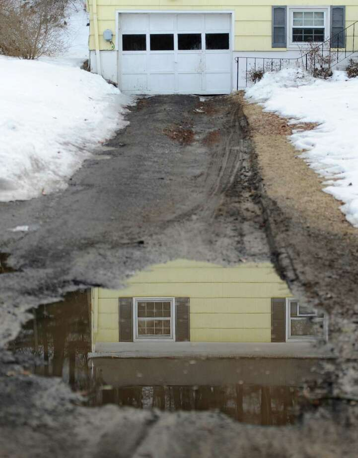 Standing water in a driveway along Hillside Court shows the reflection of a house in Brookfield, Conn. Friday, March 14, 2014.  The Limekiln Brook runs alongside Hillside Court and Hillside Circle, passing through many of the properties, and causes severe flooding and standing water when it rains. Photo: Tyler Sizemore / The News-Times