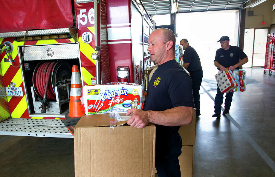 Houston Fire Department Captain Art Meade, left, firefighter Brian Wick, center, and Engine Operator Sammy Robinson, right, carry their Charmin toilet paper to be stacked at station 56, Wednesday, March 19, 2014, in Houston. As part of the Charmin Relief Project, the company donated a year's supply of toilet paper to one firehouse in every state. Photo: Cody Duty, Houston Chronicle / © 2014 Houston Chronicle