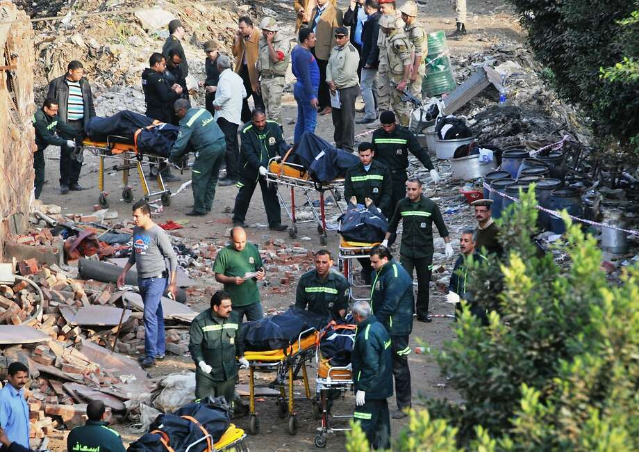 Egypt's medical staff members carry bodies out of the site of a gun battle where several militants and a few military officers were killed in Arab Sharkas village, north of Cairo, Egypt, Wednesday, March 19, 2014. Egyptian security forces raided a warehouse suspected of being a militants' bomb factory on Cairo's outskirts, sparking an hourslong battle Wednesday with gunmen that left a few military officers and several militants dead, the Interior Ministry said. (AP Photo) Photo: Associated Press
