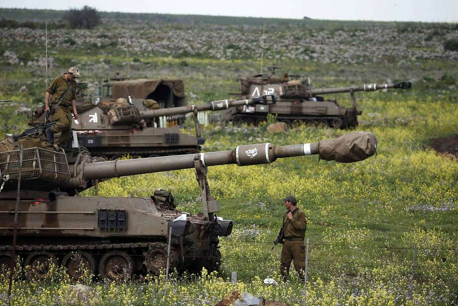 An Israeli soldier stands beside an artillery unit in the Golan Heights. Israeli air attacks were the most intense exchange across the cease-fire line since the Syrian war began. Photo: Ronen Zvulun, Reuters