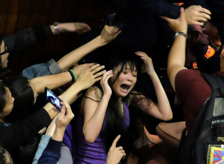 A protester cries out as police officers storm the blocked entrance of the Taiwanese parliament in Taipai. About 200 students and other activists protesting the ruling Kuomintang Party's contentious trade agreement with China took over the main chamber of the parliament overnight and barricaded doors. Photo: Sam Yeh, AFP/Getty Images