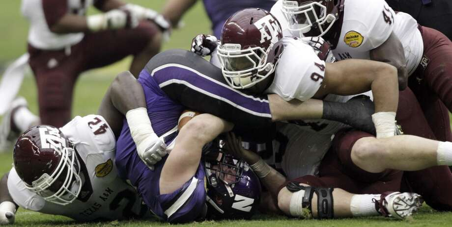 Northwestern running back Jacob Schmidt, center, is crushed by Texas A&M's Kirby Ennis (42), Damontre Moore (94), and Steven Jenkins (45) during the first quarter of the Car Care Bowl NCAA college football game Saturday, Dec. 31, 2011, in Houston. (AP Photo/David J. Phillip) Photo: David J. Phillip, AP
