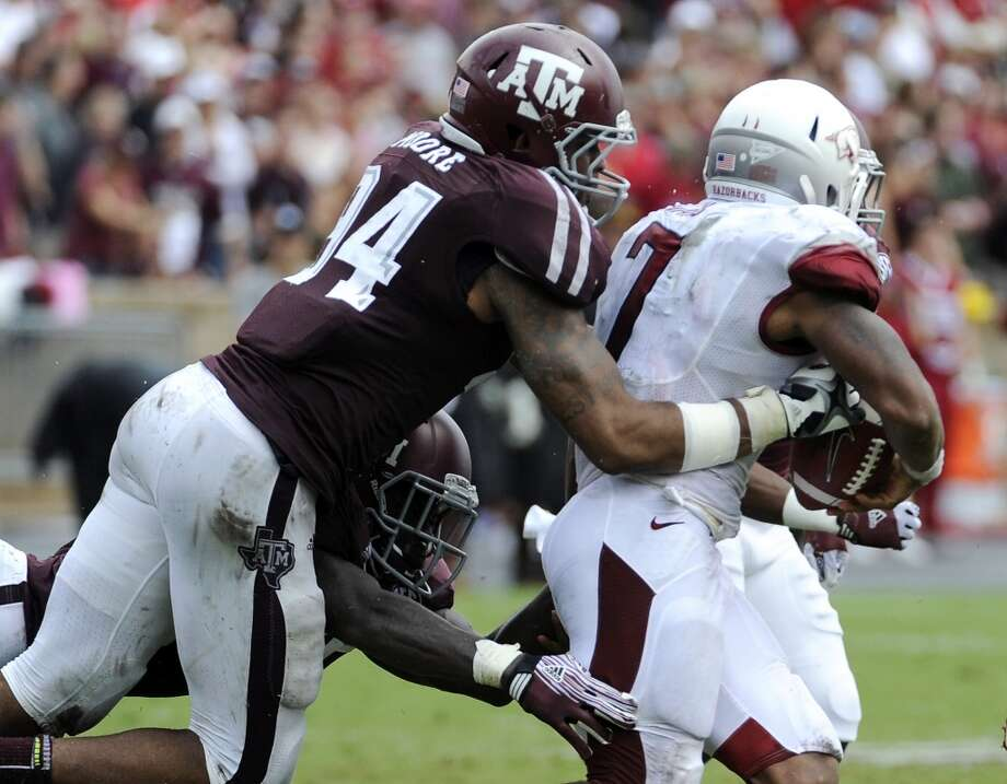 Texas A&M defensive lineman Damontre Moore (94) knocks the ball loose from Arkansas running back Knile Davis (7) during the third quarter of an NCAA college football game Saturday, Sept. 29, 2012, in College Station, Texas. A&M's Tramain Jacobs recovered the ball and scored a touchdown. (AP Photo/Pat Sullivan) Photo: Pat Sullivan, Associated Press