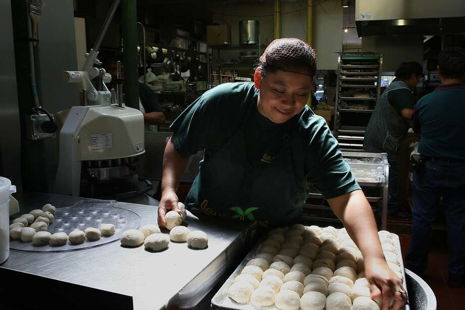 Julieta Cifuentes balls up tortilla dough at the popular La Palma Mexicatessen. Photo: Liz Hafalia, The Chronicle