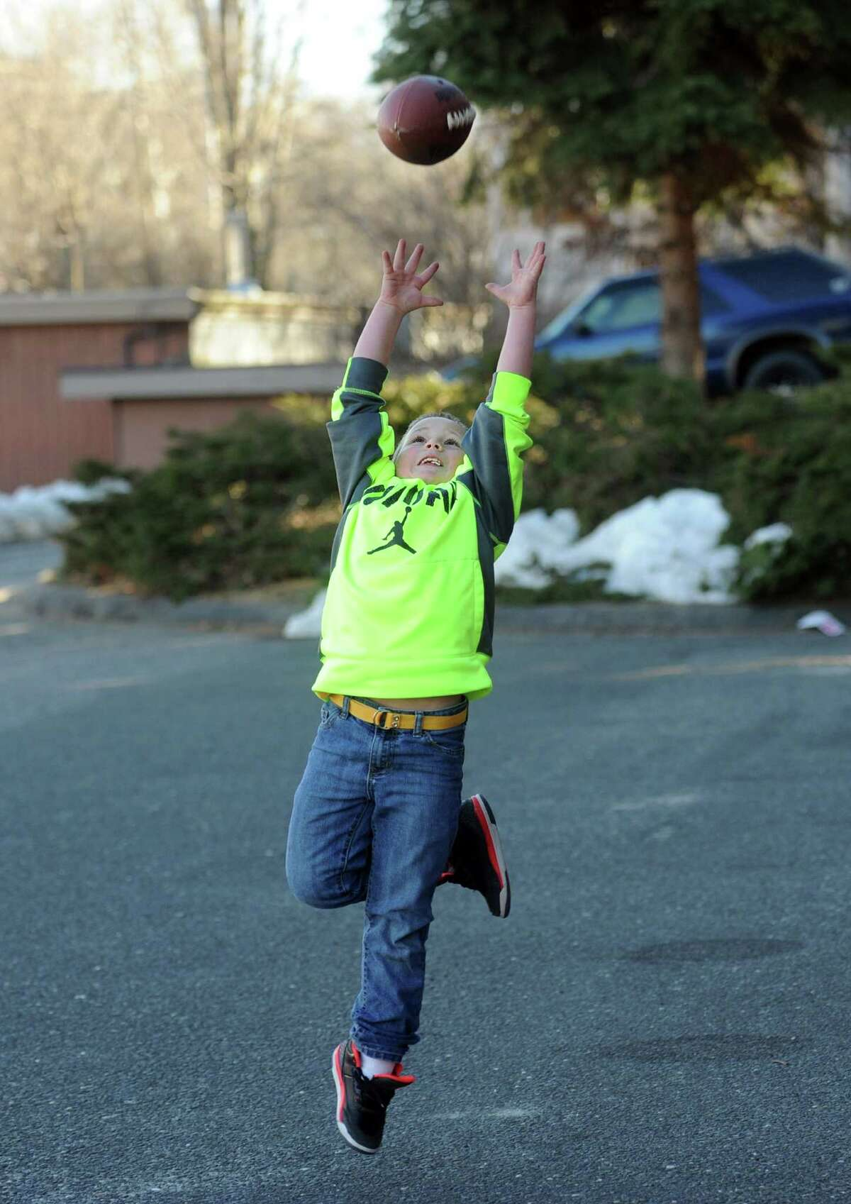 Nine-year-old Julian Basta, of Shelton, practices his passing and catching game with his father Tuesday, Mar. 18, 2014, at their home in Shelton, Conn. Basta has played for the Stratford Redskins for the past 5 years.