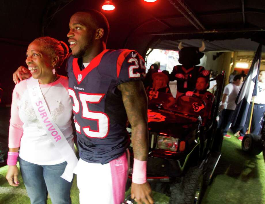 Houston Texans cornerback Kareem Jackson escorts his mother, Rossalyn Jackson, on to the field for a game-day breast cancer awareness program. Photo: Brett Coomer, Staff / © 2013  Houston Chronicle