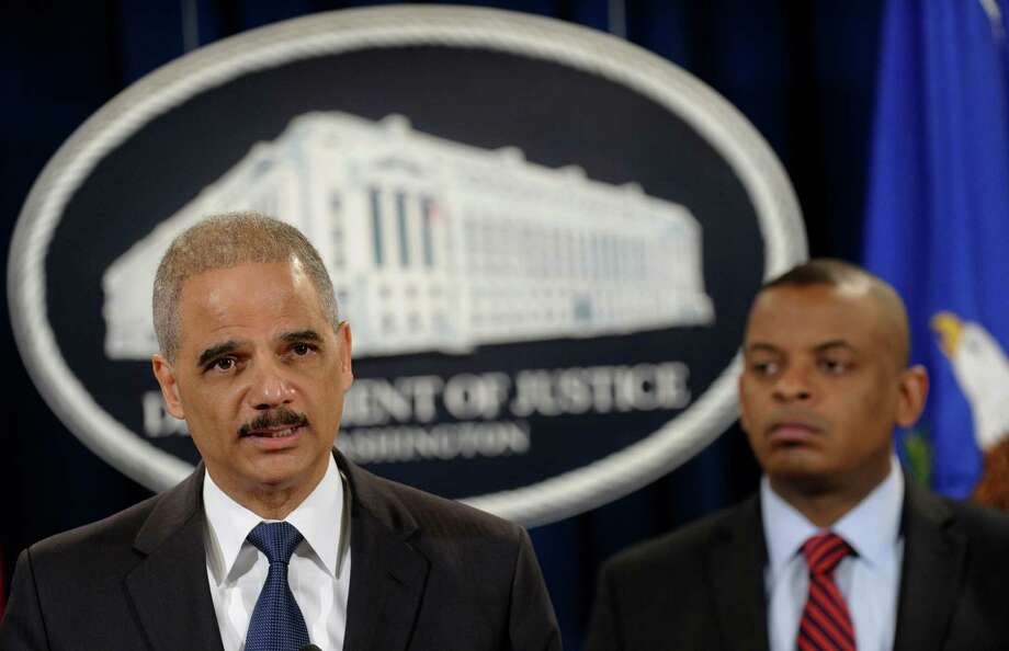 Attorney General Eric Holder, left, accompanied by Transportation Secretary Anthony Foxx, announces a $1.2 billion settlement with Toyota over its disclosure of safety problems, Wednesday, March 19, 2014, during a news conference at the Justice Department in Washington. (AP Photo/Susan Walsh) ORG XMIT: DCSW102 Photo: Susan Walsh / AP