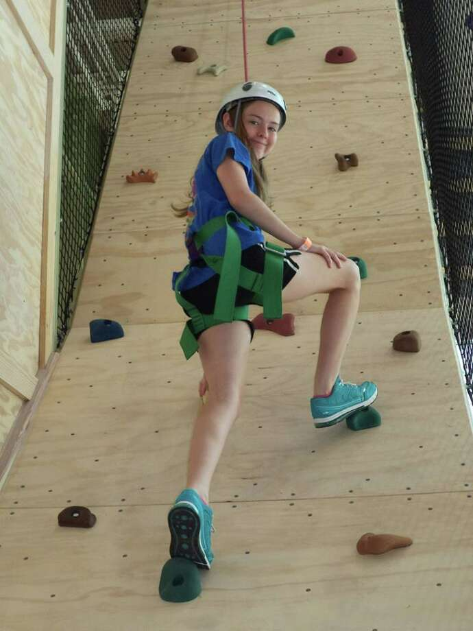 Payton Perry climbs a wall at Camp for All during a recent session. Photo: Photo Courtesy Of Epilepsy Found