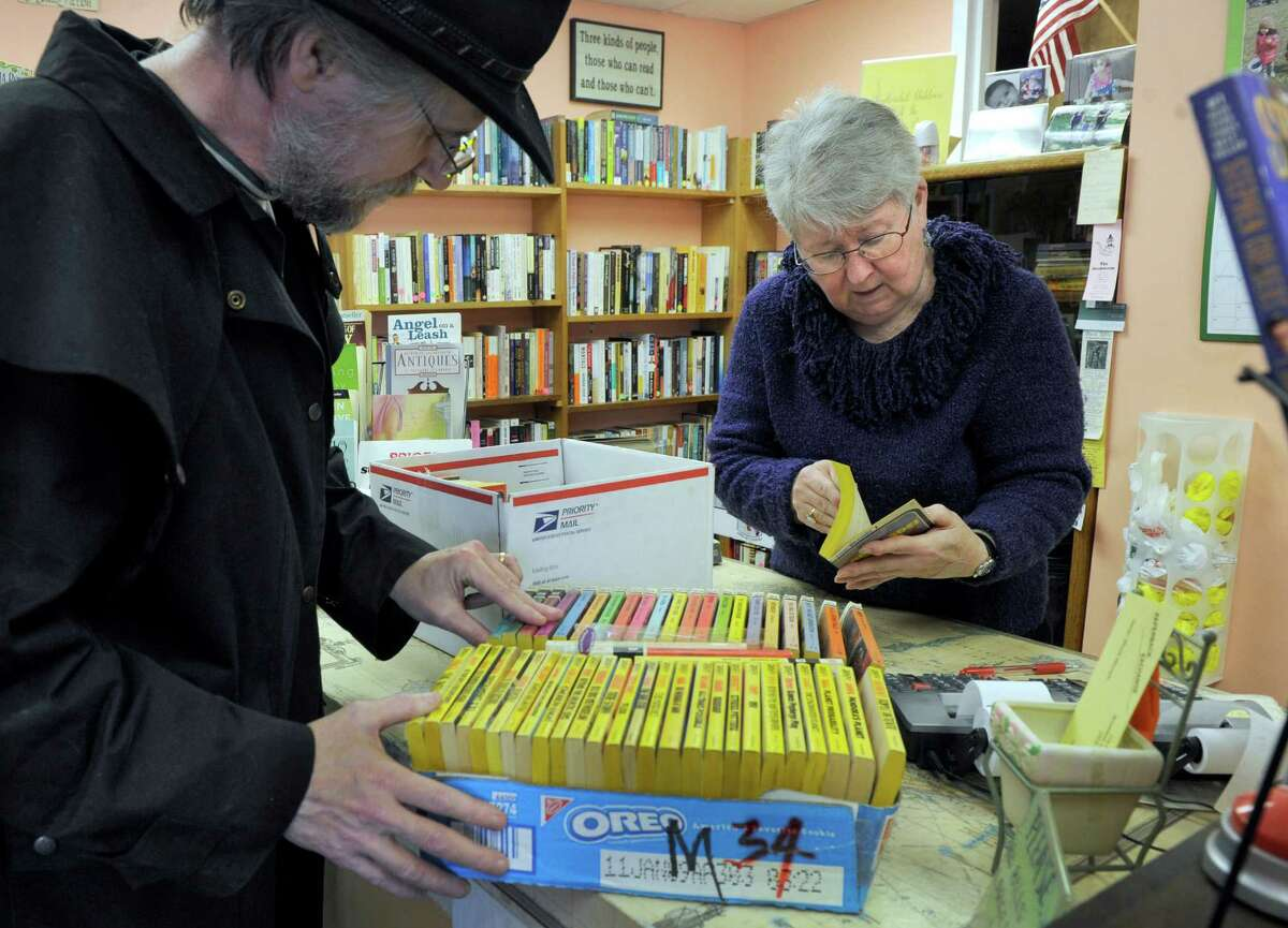 Winnie Mercado, 67, owner of The Paperback Exchange in Brookfield, Conn., helps long-time customer Douglas Stuart, 57, of Brookfield, Wednesday, March 19, 2014.