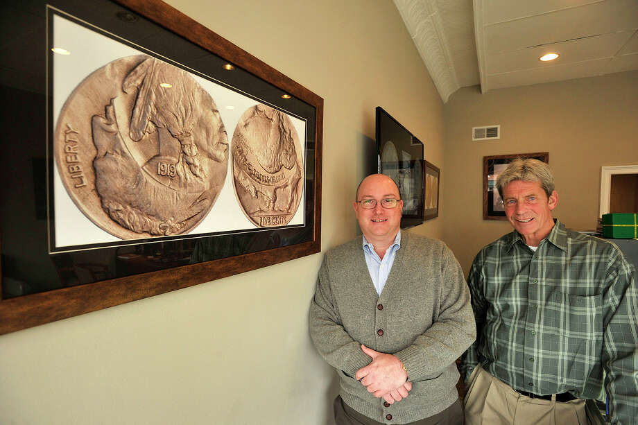 Co-owners Chris Moran, left, and Jerry Jackson pose next to a print of one of their more unique coins, a 1919 double-struck inverted buffalo nickel, for sale at their shop, The Happy Coin, in the Cos Cob neighborhood of Greenwich, Conn., on Wednesday, March 19, 2014. Photo: Jason Rearick / Stamford Advocate