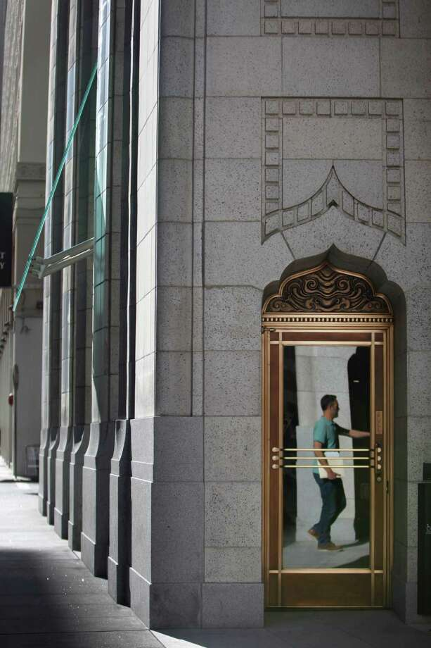 A door near the main entrance of 140 New Montgomery St. reflects a passerby. Photo: Lea Suzuki / The Chronicle / ONLINE_YES