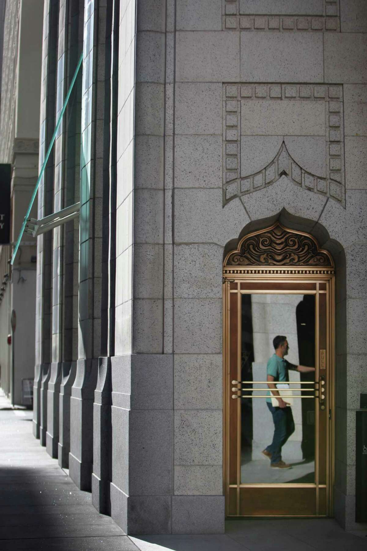 A door near the main entrance of 140 New Montgomery St. reflects a passerby.