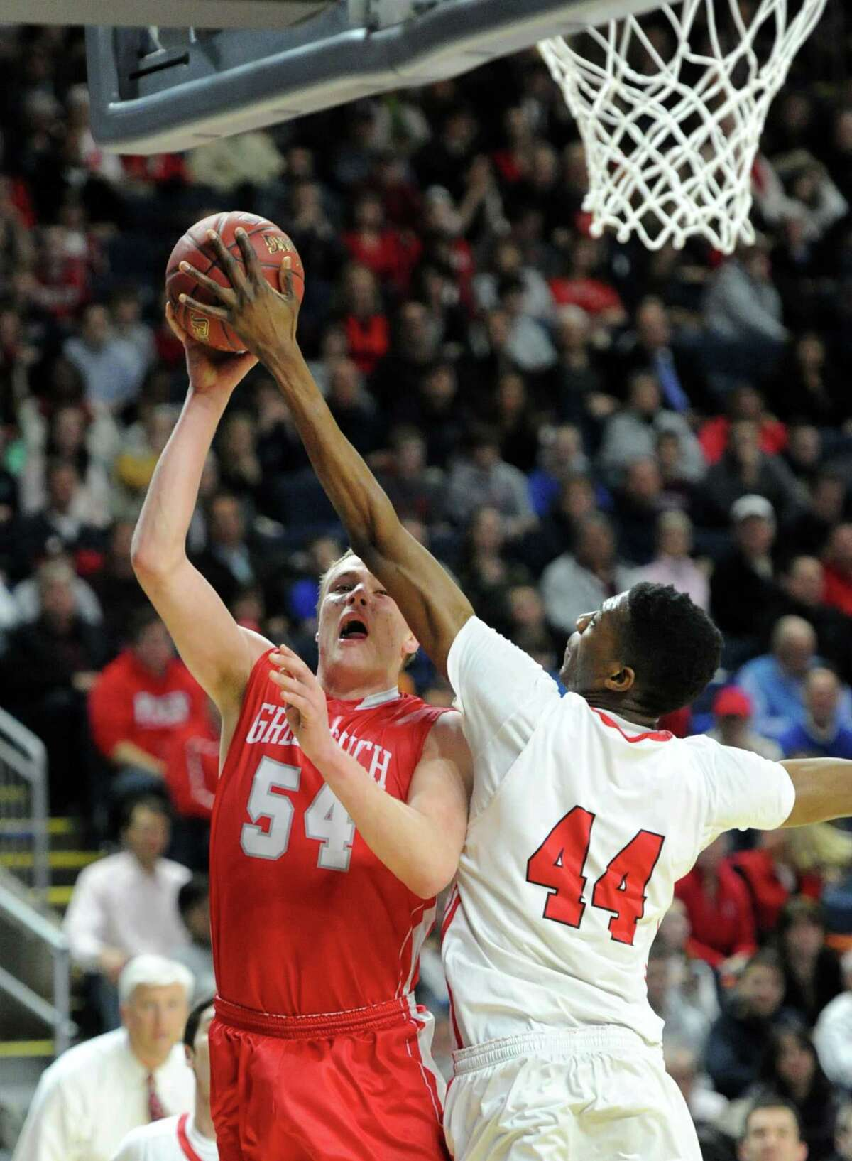 At right, Paschal Chukwu (#44) of Fairfield Prep blocks the shot of Alex Wolf (#54 ) of Greenwich during the Class LL boys basketball semi-final game between Fairfield Prep and Greenwich High School at the Webster Bank Arena in Bridgeport, Conn., Wednesday, March 19, 2014.