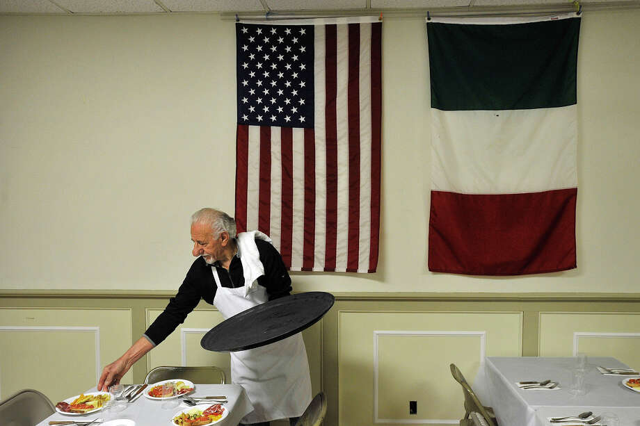 Under the American and Italian flags, Pasquale Mallozzi sets the tables for the first course of what will be a seven course meal as part of the monthly dinners at the Minturnese Social Club in Stamford, Conn., on Wednesday, March 19, 2014. The social club will be celebrating 75 years in Stamford on Saturday. Photo: Jason Rearick / Stamford Advocate