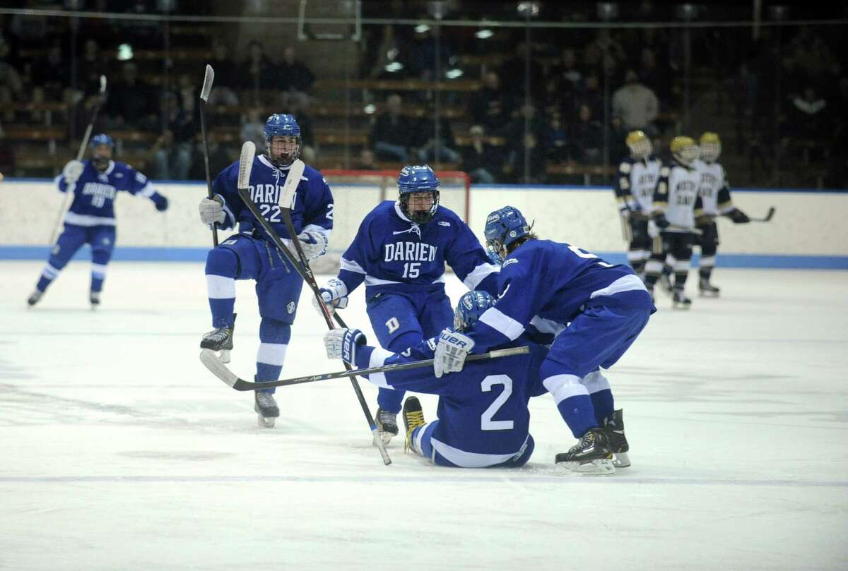 Darien teammates celebrate their tie-breaking goal Wednesday, Mar. 19, 2014, during the boys ice hockey Division I semifinals against Notre Dame-Fairfield at Ingalls Rink in New Haven, Conn.
