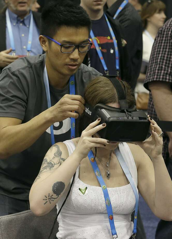David Ninh helps put an Oculus virtual reality headset onto Lana Ansay at the Game Developers Conference 2014 in San Francisco, Wednesday, March 19, 2014. (AP Photo/Jeff Chiu) Photo: Jeff Chiu, Associated Press