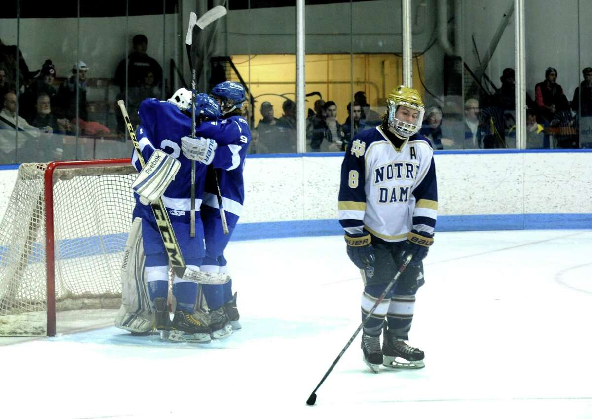 Notre Dame-Fairfield captain Craig Hessenius skates off the ice as Darien celebrates their win Wednesday, Mar. 19, 2014, in the boys ice hockey Division I semifinals at Ingalls Rink in New Haven, Conn.