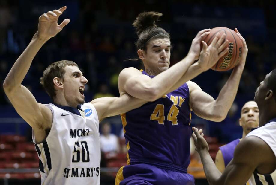 Albany center John Puk (44) pulls a rebound away from Mount St. Mary's center Taylor Danaher (50). Photo: Al Behrman, Associated Press