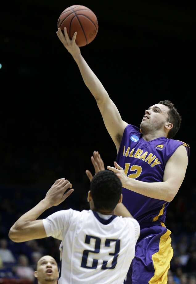 Albany guard Peter Hooley (12) drives against Mount St. Mary's guard Julian Norfleet (23). Photo: Al Behrman, Associated Press