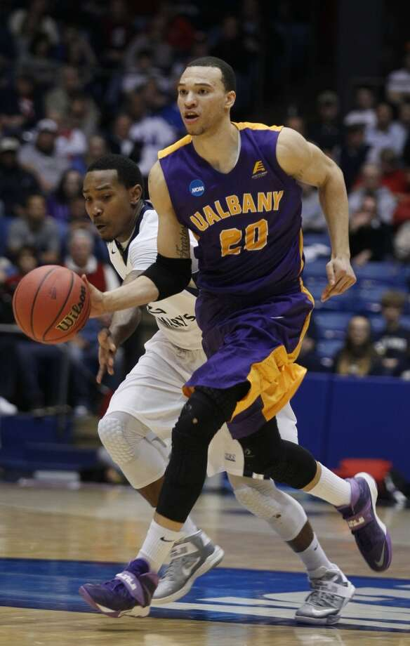 Albany forward Gary Johnson (20) brings the ball up court against Mount St. Mary's. Photo: Skip Peterson, Associated Press