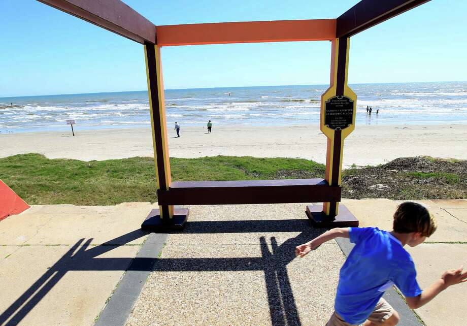 People walk by the site of the historic Balinese Room pier on the Seawall, Tuesday, March 18, 2014, in Galveston. Photo: Karen Warren, Houston Chronicle / © 2014 Houston Chronicle