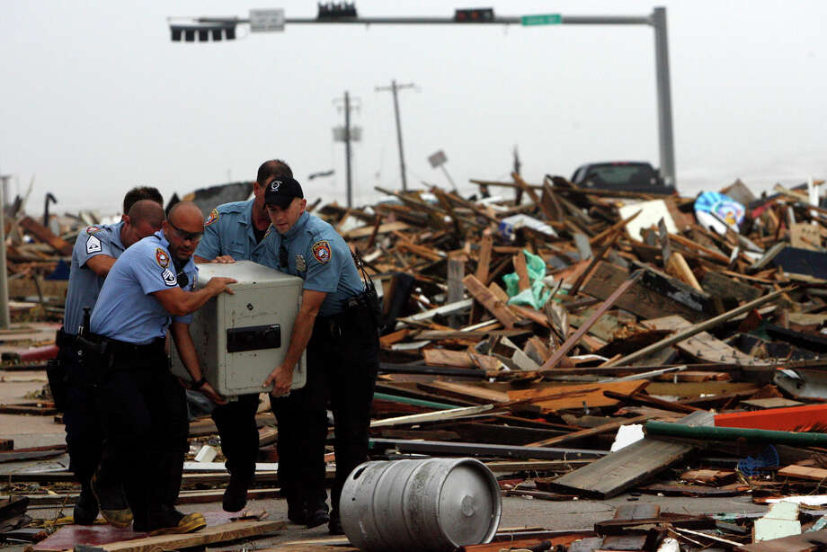 "Galveston police officers remove a safe from the rubble where the Hooters restaurant was decimated by Hurricane Ike on Seawall Blvd. Saturday, Sept. 13, 2008. The storm took out the Balinese Room, Murdock's Pier and Hooters along the seawall. ""I saw the Balinese Room roll into the Murdock and Mermaid Pier and explode, literally exploded,"" Daryl Secteau a Galveston resident said. Photo: Johnny Hanson, Houston Chronicle / Houston Chronicle"