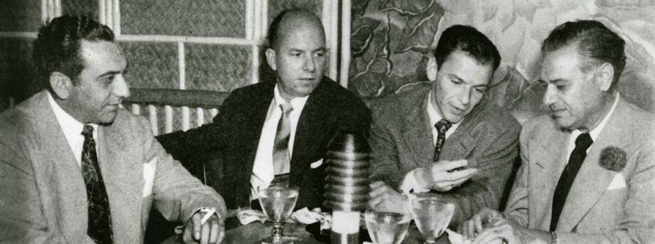 Frank Sinatra, appearing at Houston's Shamrock Hotel during Galveston's gambling heyday, dropped down to the Balinese Room on his night-off to socialize with, from left,  Anthony Fertitta, Jimmy Van Heusen, and Sam Maceo. Photo: Rosenberg Library,  Galveston / handout