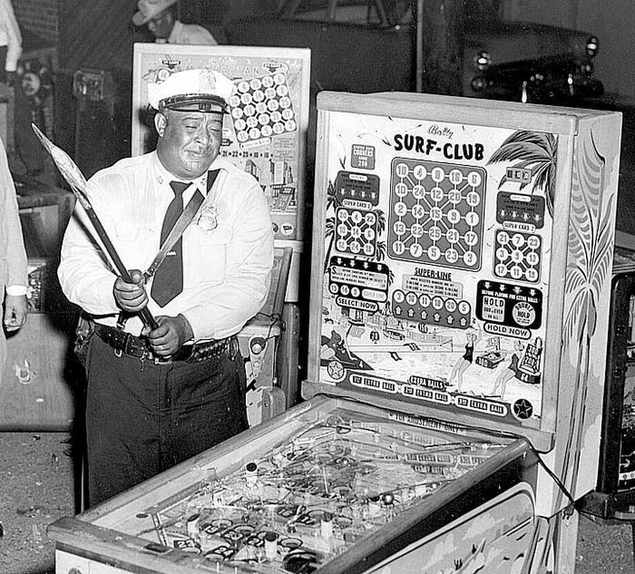 Lawmen smashed pinball machines, slot machines and other gambling devices in 1957 after state Attorney general Will Wilson obtained court injunctions to shut down Galveston gambling house. Thousands of machines were destroyed or dumped in Galveston Bay before the officers left. Photo: Tom Colburn, Houston Chronicle / Houston Chronicle