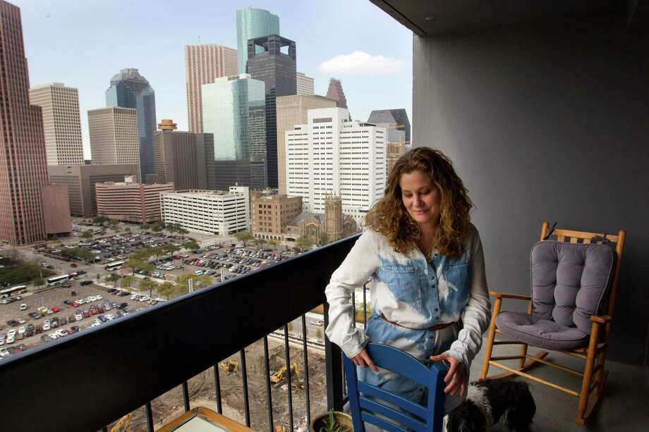Angela Touchstone has a grand vista of the Houston skyline from her balcony at Houston House Apartments, near the Toyota Cener. She moved there from the suburbs more than two years ago. Photo: Brett Coomer, Staff / © 2014 Houston Chronicle