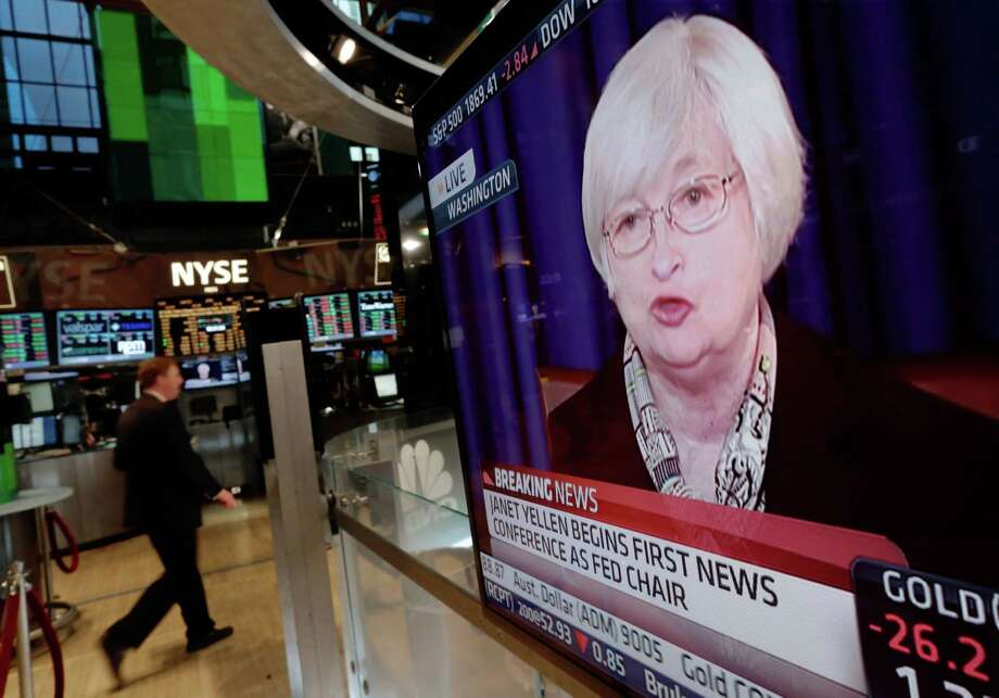 A television screen on the floor of the New York Stock Exchange shows Federal Reserve Chair Janet Yellen's first news conference, in Washington D.C., Wednesday, March 19, 2014.  The Federal Reserve is seeking to clarify when it might start to raise short-term interest rates from record lows. The Fed also says it will cut its monthly long-term bond purchases by another $10 billion to $55 billion because it thinks the economy is strong enough to support further improvements in the job market. (AP Photo/Richard Drew) Photo: Richard Drew, STF / AP