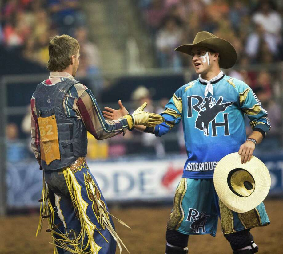 Tyler Smith shakes hands with bullfighter Chuck Swisher, right, after the BP Super Series Semifinal 1 Bull Riding competition at Reliant Stadium on Wednesday, March 19, 2014, in Houston. Photo: Marie D. De Jesus, Houston Chronicle / © 2014 Houston Chronicle