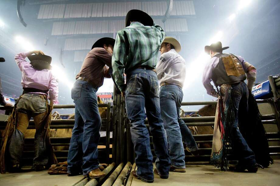 Bareback riders and staff stand behind the chute to prepare for the BP Super Series Semifinal 1 bareback riding competition during the Houston Livestock Show and Rodeo, Wednesday, March 19, 2014, in Houston. Photo: Marie D. De Jesús, Houston Chronicle / © 2014 Houston Chronicle