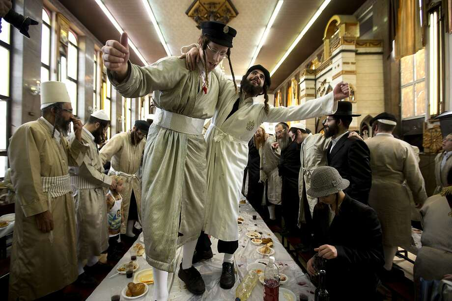 Ultra-Orthodox men in costumes, above, dance atop a table at a rabbinical seminary in Jerusalem. Photo: Sebastian Scheiner, Associated Press