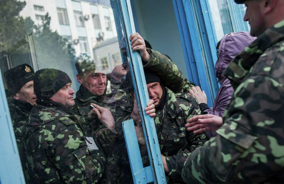 Pro-Russian force members get through an entrance to the Ukrainian Navy headquarters in Sevastopol, Crimea, and soon after raise the Russian flag in the square by the headquarters. Photo: Andrew Lubimov / Associated Press / AP
