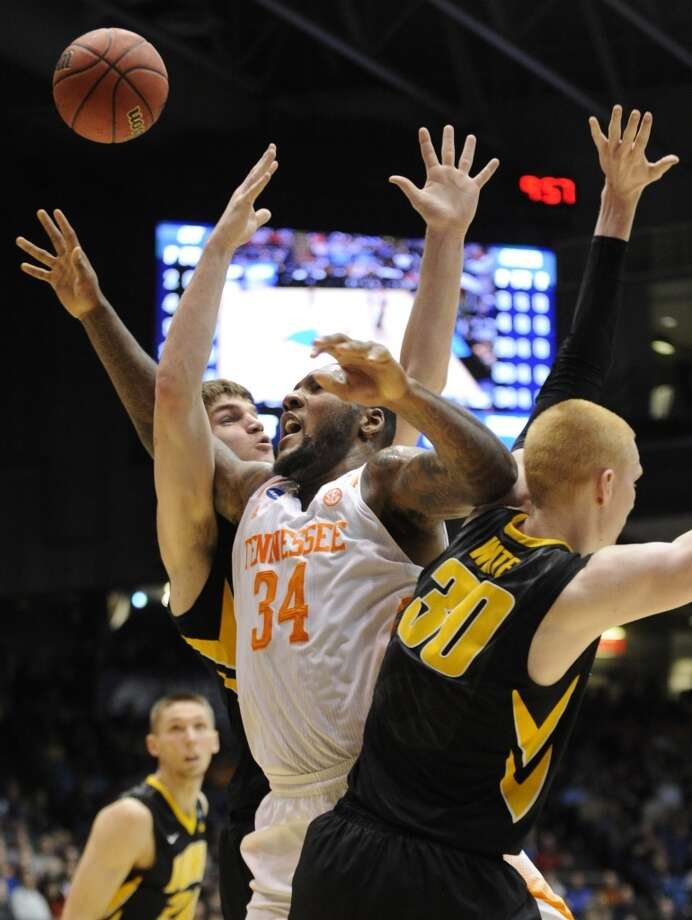 Tennessee forward Jerrone Maymon (34) reaches for a rebound against Iowa defenders. Photo: Adam Lau, Associated Press