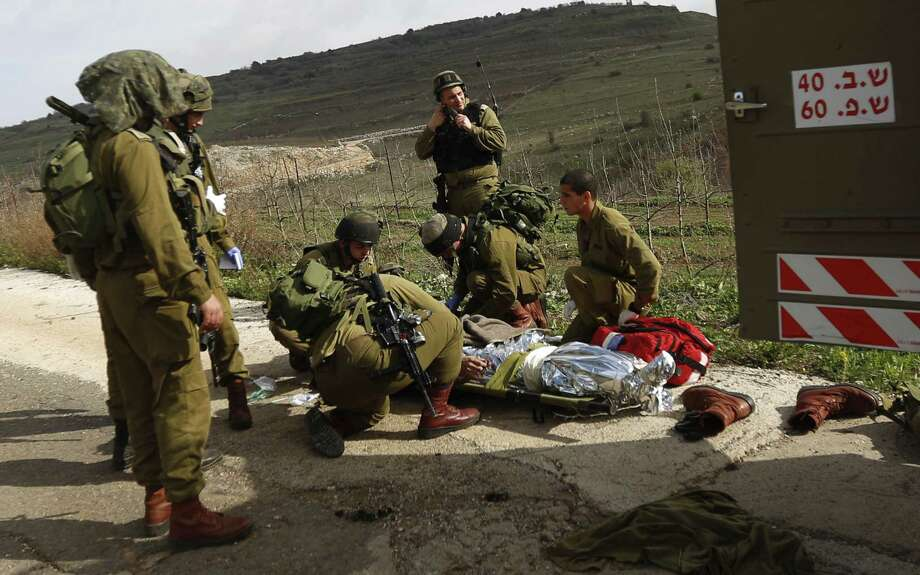 A wounded Israeli soldier is treated in the Golan Heights after a roadside bombing Tuesday. Israel later hit targets in Syria. Photo: Jinipix / Associated Press / AP