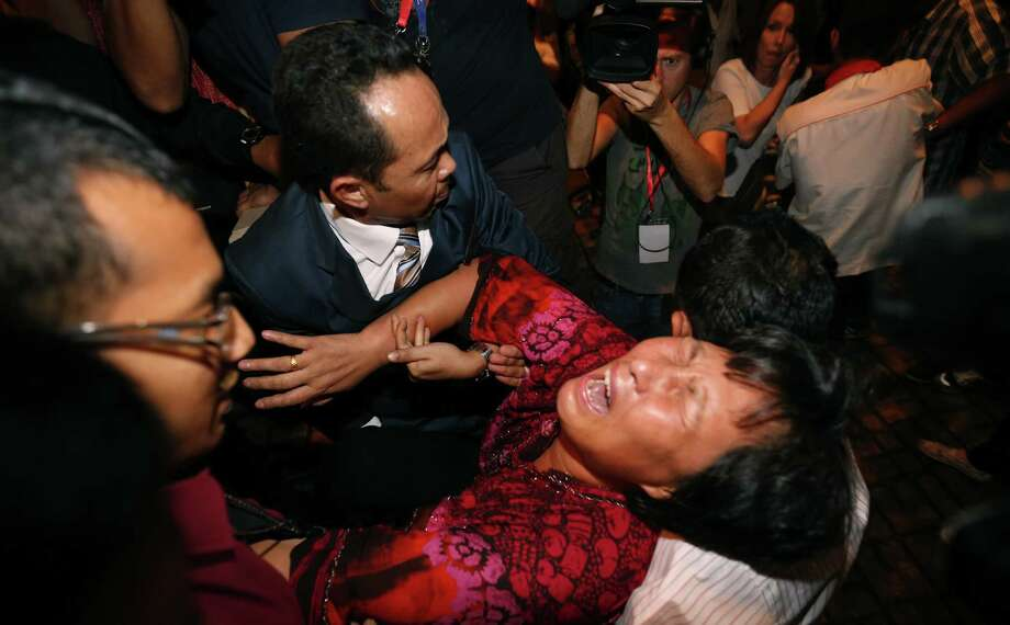 A Chinese relative of a passenger aboard the missing Malaysia Airlines plane is carried out by security officials as she protests before a news conference near Kuala Lumpur's airport. Photo: Vincent Thian / Associated Press / AP