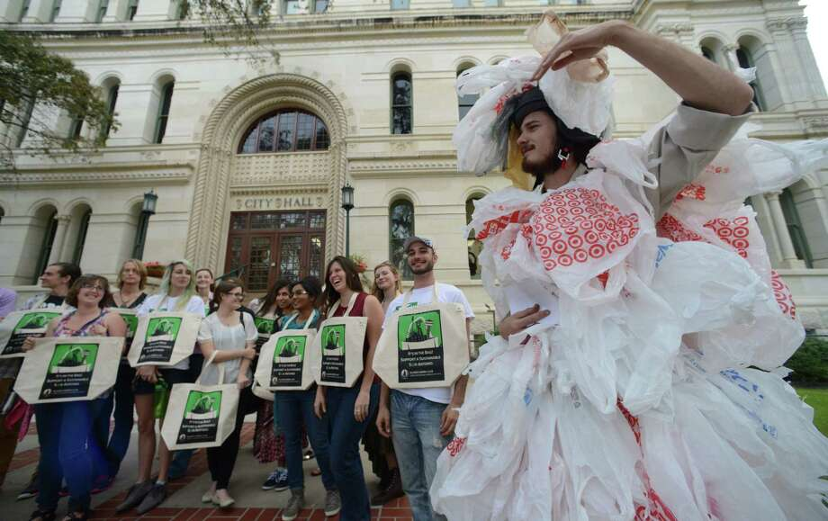 "Chris Yardy (right), playing the part of a ""plastic bag monster,"" entertains during a press conference outside City Hall by people seeking to ban single-use bags in San Antonio. Photo: Billy Calzada / San Antonio Express-News / San Antonio Express-News"