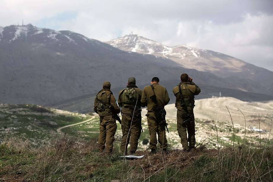 TOPSHOTS Israeli soldiers deployed on the border with Syria observe Syrian territory from Israeli side of the border near the Druze village of Majdal Shams on March 19, 2014 in the Israeli-annexed Golan Heights. Israel launched air raids against Syrian army positions and issued a stark warning to Damascus just hours after a bomb on the occupied Golan Heights wounded four of its soldiers. AFP PHOTO/MENAHEM KAHANAMENAHEM KAHANA/AFP/Getty Images Photo: Menahem Kahana, AFP/Getty Images