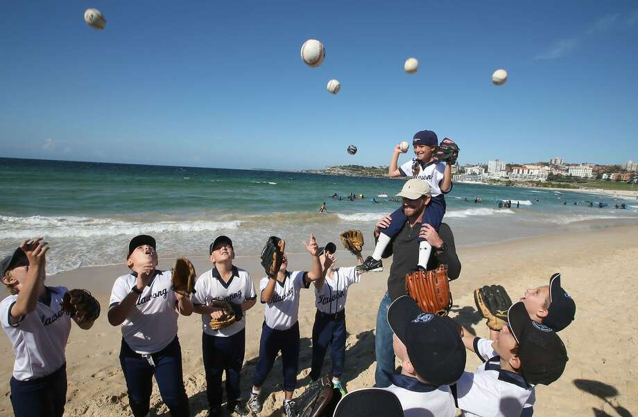 Ten-year-old Taylor Angelis, top right, sits on the shoulders of the Los Angeles Dodgers' Chris Withrow as little league players toss ball into the air at Bondi Beach in Sydney, Wednesday, March 19, 2014. The Major League Baseball season-opening two-game series between the Los Angeles Dodgers and Arizona Diamondbacks in Sydney will be played this weekend. (AP Photo/Rick Rycroft) Photo: Rick Rycroft, Associated Press