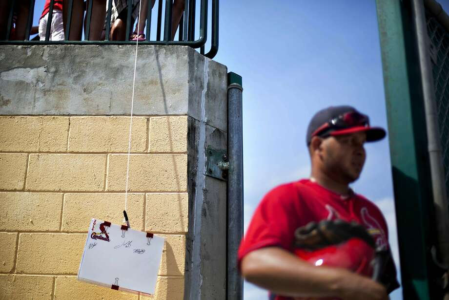 Fans lower a sheet of paper with string hoping to get an autograph from St. Louis Cardinals' Jhonny Peralta, right, as he leaves the field through the right field door during the eighth inning of an exhibition spring training baseball game against the Minnesota Twins, Wednesday, March 19, 2014, in Jupiter, Fla. (AP Photo/David Goldman) Photo: David Goldman, Associated Press