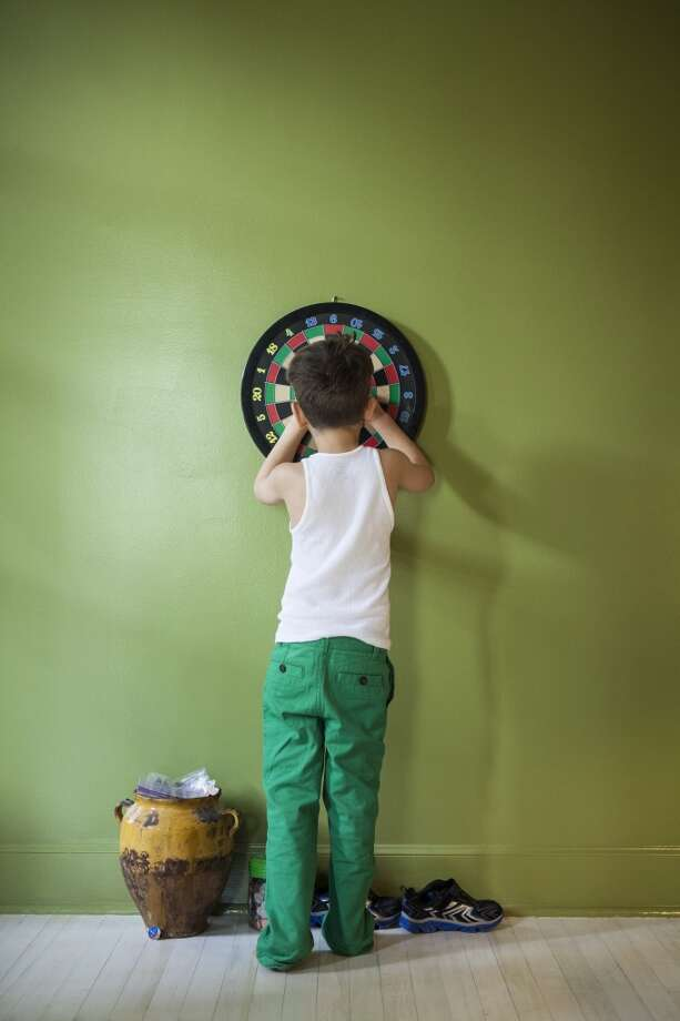 Play darts in the basement. Parents these days usually buy 'safer' magnetic boards for their kids although games such as darts are a lot less popular in general because children prefer video games. Photo: Catherine Ledner, Getty Images