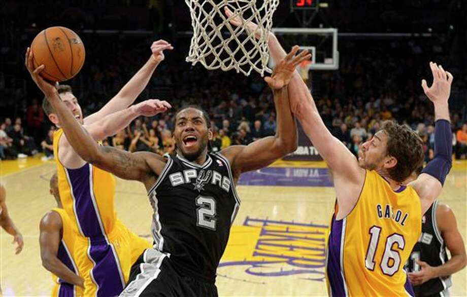 San Antonio Spurs forward Kawhi Leonard, center, goes up for a shot as Los Angeles Lakers forward Ryan Kelly, left, and center Pau Gasol, of Spain, defend during the second half of their NBA basketball game, Wednesday, March 19, 2014, in Los Angeles. The Spurs won 125-109. (AP Photo/Mark J. Terrill) Photo: Mark J. Terrill, AP / AP