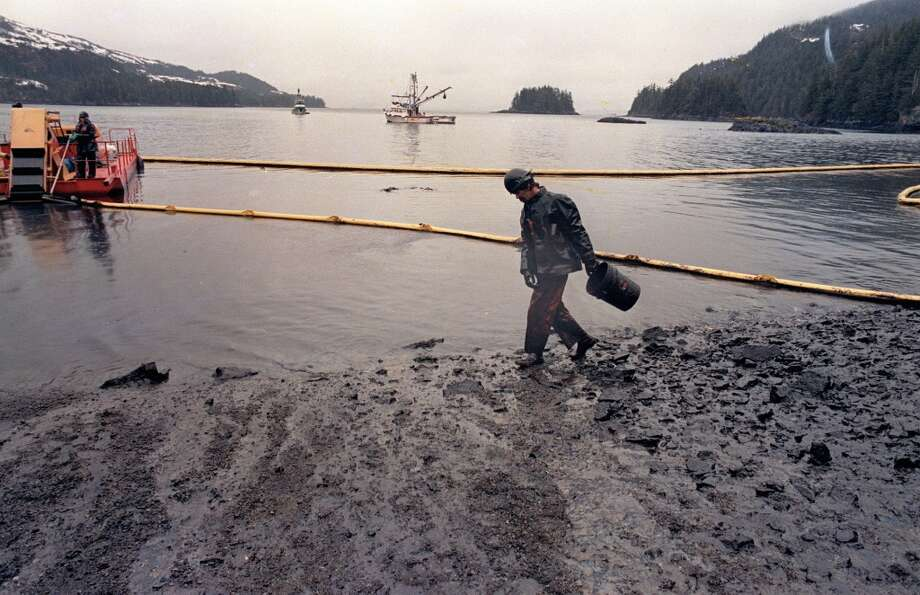 In April 1989, a worker makes his way across the polluted shore of Block Island,  Alaska, as efforts are underway to test techniques to clean up the oil spill of the tanker Exxon Valdez in Prince William Sound.  The worker periodically uses the bucket to scoop up oil washing back onto shore from the containment booms.  Nearly 25 years after the Exxon Valdez oil spill off the coast of Alaska, some damage heals, some effects linger in Prince William Sound. Photo: John Gaps III, ASSOCIATED PRESS