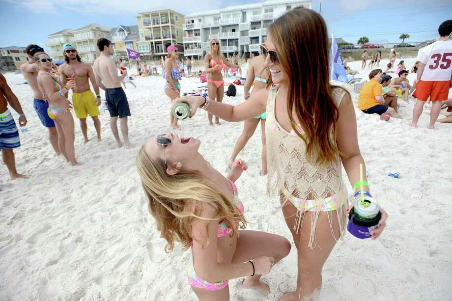 University of Tennessee spring breakers Bree Thomas, right, pours a beer into the mouth of Rachael Dubois on Tuesday March 18, 2014 in Destin, Fla. Photo: Nick Tomecek), AP / Northwest Florida Daily News