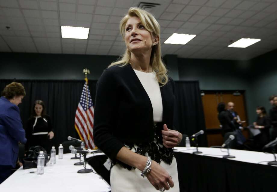 In this Jan. 9, 2014 file photo, Texas Sen. Wendy Davis heads over to speak to reporters after an education roundtable meeting in Arlington, Texas. Davis' rise from a teenage single mother living in a trailer park to Harvard Law School is a centerpiece of her campaign for Texas governor, but some of the details of her personal story may be fuzzier than first thought. (AP Photo/LM Otero, File) Photo: Associated Press