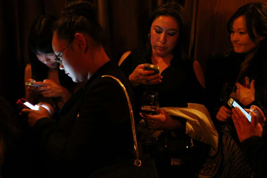 Susannah Shum (left), Selina Ng, Cassandra Louie and Anna Lee check their phones at a party for Poshmark, a site selling used clothing and accessories. Photo: Carlos Avila Gonzalez, The Chronicle