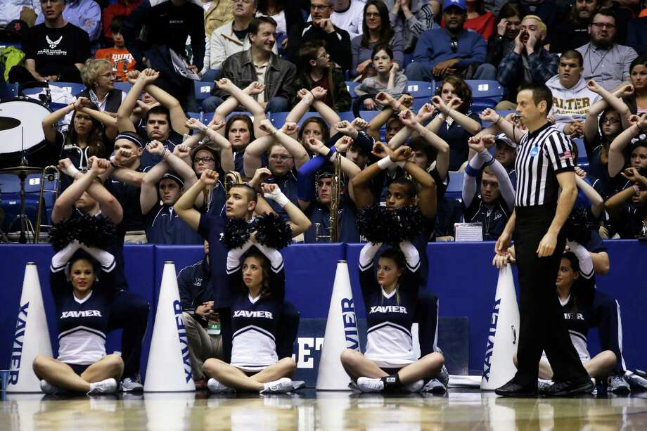 The Xavier cheerleaders and band make X's while a player shoots free throws against North Carolina State in the second half of a first-round game of the NCAA college basketball tournament, Tuesday, March 18, 2014, in Dayton, Ohio. (AP Photo/Al Behrman) Photo: Al Behrman, Associated Press / AP