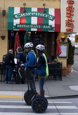 Visitors riding segways make their way up past the Cioppino's restaurant on Sunday, Mar. 2, 2014 in San Francisco, Calif. Cioppino's is a  a popular restaurant at the wharf and manages to keep a fairly old-school menu of San Francisco specialties
